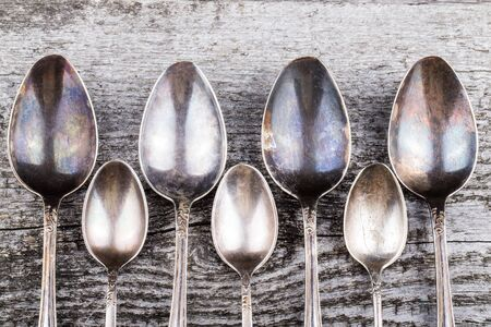 melchior: Antic metal spoons on old wooden board. Selective focus.