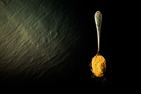 karri: Old metal spoon with spices on a black background. Toned.
