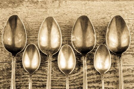 tarnished: Antic metal spoons on old wooden board. Selective focus. Toned.