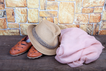 moccasins: Straw hat, pink scarf and moccasins on a wooden table in front of a stone wall.