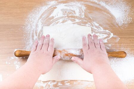 roll out: Plump womens hands roll out the dough on a light wooden table.