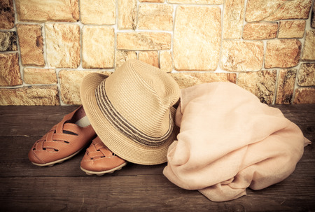 moccasins: Straw hat, pink scarf and moccasins on a wooden table in front of a stone wall. Toned.