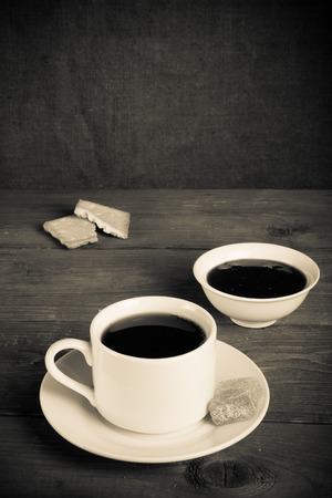 jam biscuits: Tazza di t� con marmellata, biscotti e marmellate sul vecchio tavolo di legno sullo sfondo di tela. Tonica.