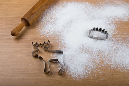 Rolling pin, forms for baking and flour sprinkled on a light wooden table. photo