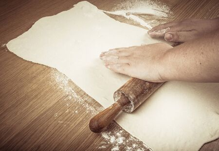 roll out: Plump womens hands roll out the dough on a light wooden table. Toned. Stock Photo