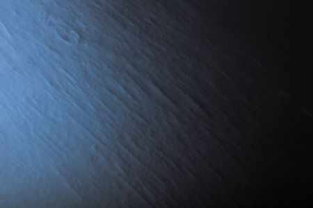 varying: Black textured wall with varying light conditions. Background. Toned blue. Stock Photo