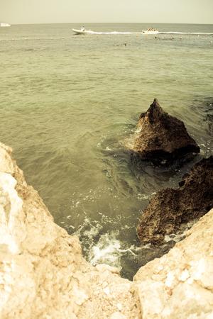 Motor boats, buoys on the sea and rocky coast. Egypt. Shallow depth of field. Toned. photo