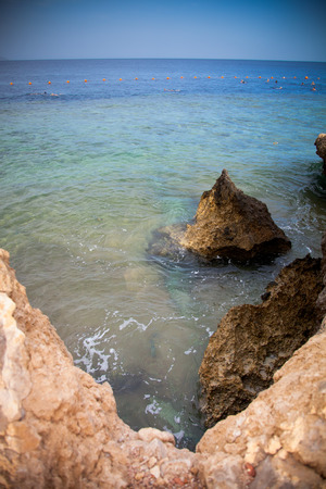 Rocky coast and buoys on the sea. Egypt. Shallow depth of field. Toned. photo