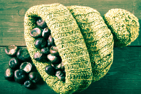 Chestnuts in a knitted hat on a old wooden table. Toned. photo