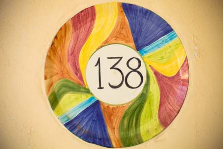 Number 138 in the middle of multicolored ceramic circle on the light wall. Toned. photo