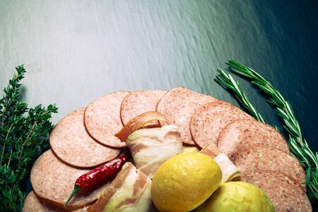 french bread rolls: plate of sliced sausage, peppers, herbs and French bread rolls on a dark background