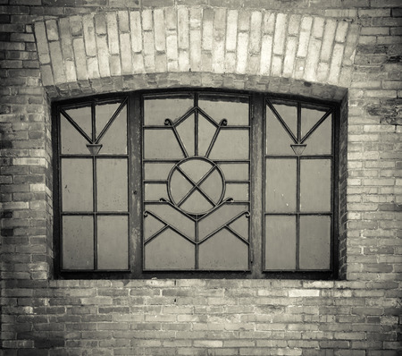 iron barred: Old wrought window in the wall of brick Stock Photo
