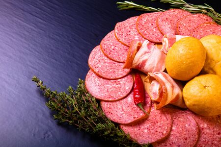 french bread rolls: plate of sliced sausage, peppers, herbs and French bread rolls on a dark background. Tinted
