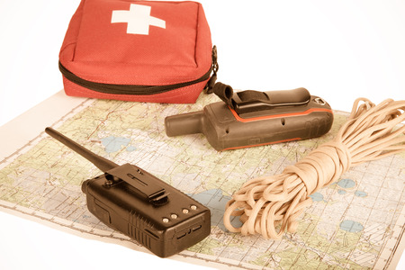 navigation aid: Map, gps navigator, portable radio, rope and first aid kit on a light background. Set lifeguard. Toned.