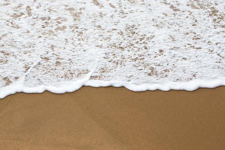 ocea: Sea foam on a sandy beach.