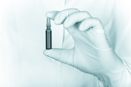ampoule: A gloved hand holding a ampoule with medicine on a background of medical coat. Toned. Stock Photo