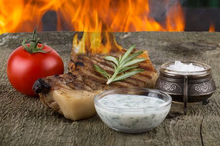 souse: Pork steak with rosemary, tomato and souse on old wooden table with flame background. Stock Photo