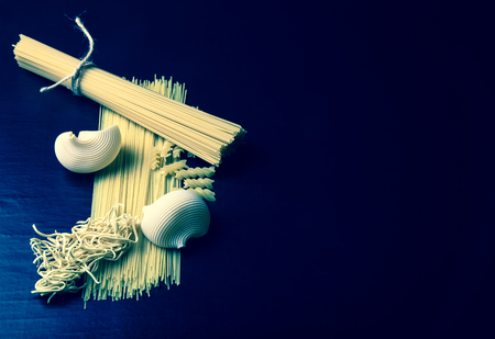 Different kinds of pasta on a black background. Space for text. Toned. photo