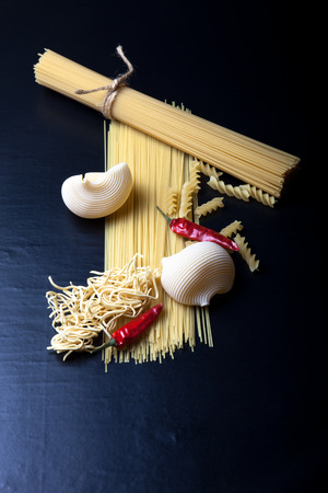 Different kinds of pasta and  red chili pepper on a black background photo