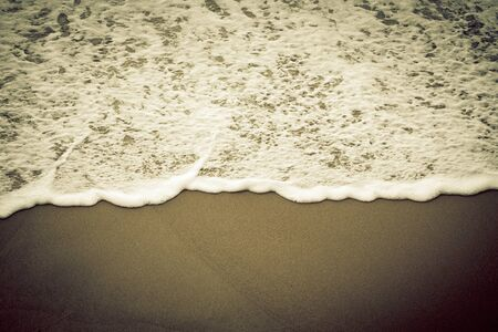 ocea: Sea foam on a sandy beach. Toned.