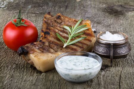 souse: Pork steak with rosemary, tomato and souse on old wooden table.