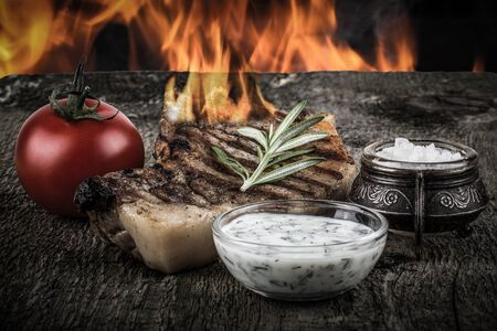 souse: Pork steak with rosemary, tomato and souse on old wooden table with flame background. Toned. Stock Photo