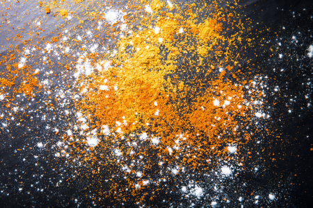 yellow flour: Red and yellow spices and flour on a black background. Selective focus. Culinary galaxy and planets. Stock Photo