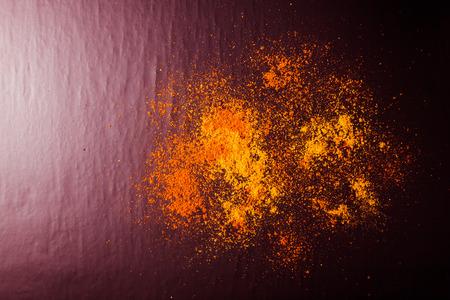 culinair: Rode en gele kruiden op een zwarte achtergrond. Selectieve aandacht. Culinair galaxy en planeten. Afgezwakt. Stockfoto
