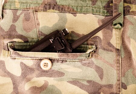 undercover: Portable radio in a pocket of pants with camouflage pattern. Toned. Stock Photo