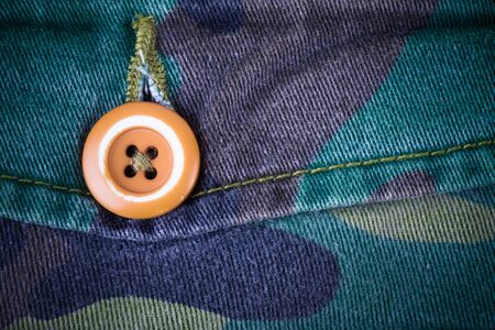 undercover: Pocket with a button on the fabric with a camouflage pattern. Background. Toned.