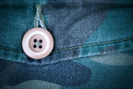 airforce: Pocket with a button on the fabric with a camouflage pattern. Background. Toned.