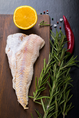 half fish: Fish filet, rosemary, red chili pepper, half a lemon and sea salt on brown cutting board on a black background. Toned. Stock Photo