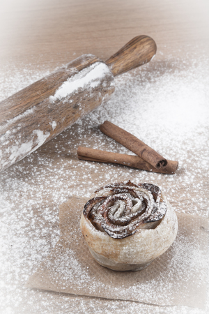 flatten: Homemade pastries with cinnamon on a light wooden table with flour. Toned.