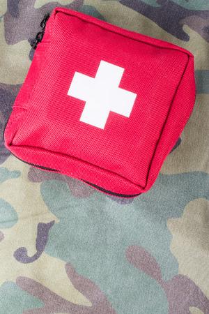 first aid kit: Botiqu�n de primeros auxilios en una tela con el patr�n de camuflaje.