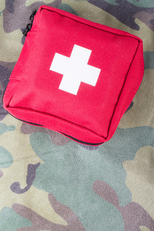 first help: First aid kit on a fabric with camouflage pattern. Stock Photo