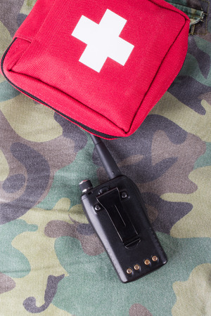 undercover: First aid kit and portable radio on a fabric with camouflage pattern. Stock Photo
