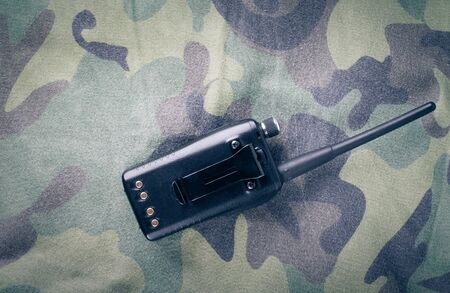 portable radio: Portable radio on a fabric with camouflage pattern. Toned. Stock Photo