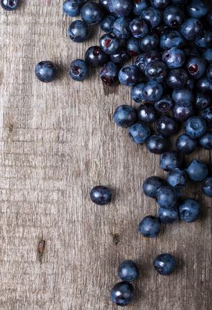 blueberries collected manually scattered on the old board.