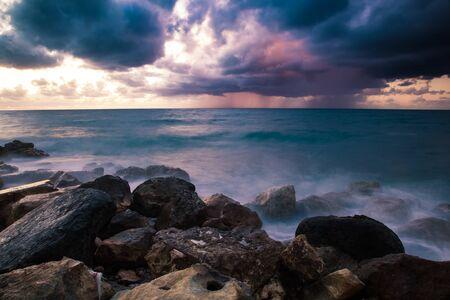 estado del tiempo: Mal tiempo. Tiempo tormentoso en la costa de piedra durante una puesta de sol. Lluvia en el horizonte. Larga exposición Foto de archivo