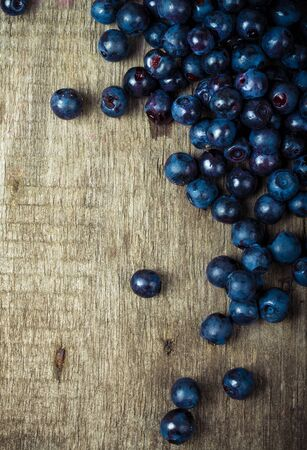 manually: blueberries collected manually scattered on the old board.