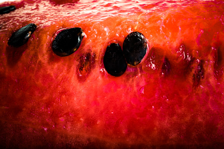 black seeds: Sweet juicy watermelon with black seeds. background. Shallow depth of field. Tinted