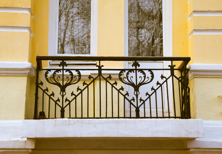 rustiness: Iron balcony on the yellow plastering wall. Toned.