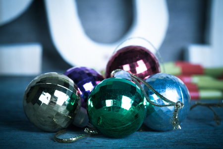 pack string: Cristmas colored balls on old wooden board with blured background. Toned.