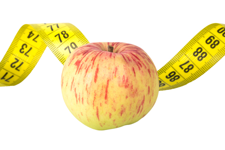 centimetre: Yellow color centimeter with black figures for measurement of length and width and fresh season apple on a white background. Stock Photo
