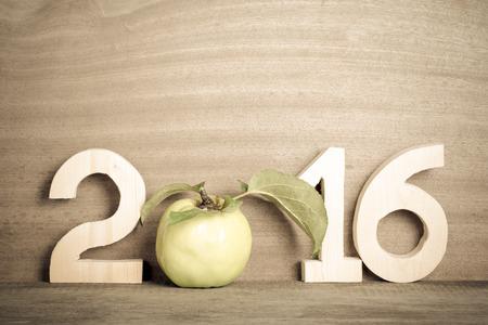De cijfers in 2016 met een appel in plaats van het getal 0 op de grijze houten achtergrond. Afgezwakt.