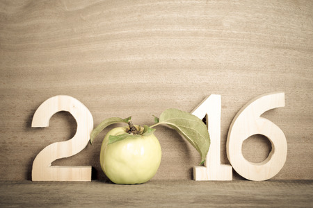 fruit tree: The figures in 2016 with an apple instead of the number 0 on the gray wooden background. Toned.