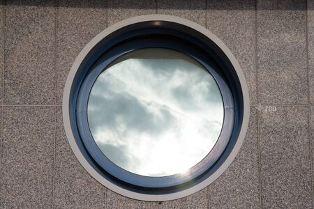 ajar: Ajar round window on the tiled granite wall - part of the urban architecture. Stock Photo