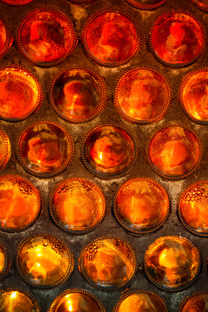 bottoms: The wall of glass bottles bottoms folded forward. Background. Selective focus. Toned.