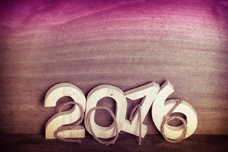 Touw en lichte houten figuren 2016 op een grijze houten achtergrond in retro vintage stijl. Ruimte voor tekst. Afgezwakt.