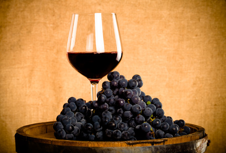 glass wine: Barrel, wineglass with some red wine and ripe grapes of wine on burlap background. Toned. Stock Photo